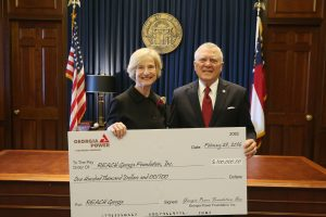 Governor Nathan Deal accepts a check from Georgia Power on behalf of the REACH Georgia Foundation from Anne Kaiser. Kaiser serves as chair for REACH Georgia Foundation and vice president of Community and Economic Development for Georgia Power.