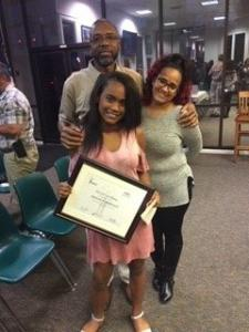 REACH Scholar with certificate and parents